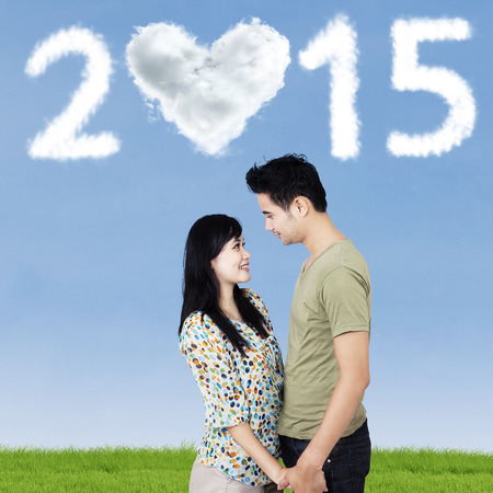 under heart: Young couple look at each other in field under heart cloud shaped number 2015