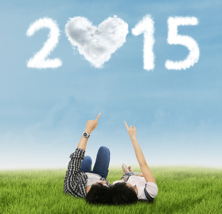Young couple lying on grass and imagined a heart shaped number 2015 photo