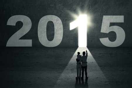 jesus standing: Silhouette of family looking at a door shaped cross with number 2015