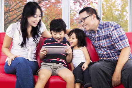 Portrait of cheerful family sharing digital tablet for play game on sofa with autumn background photo