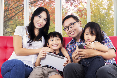 Young asian family smiling at camera while using digital tablet at home with autumn background on the window photo