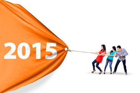 Cheerful asian people collaborate to pull a banner of 2015, isolated over white background photo