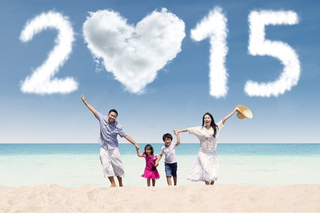 Cheerful family holding hands and run together at the beach in new year holiday photo