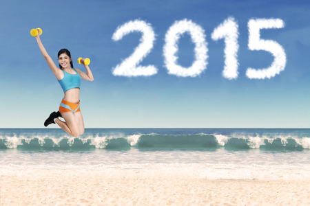 Person jumping on beach with dumbbells and cloud shaped number 2015 photo