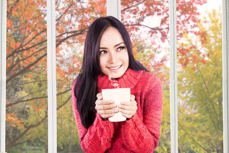warm drink: Portrait of pretty girl wearing jacket and holding warm drink at home in autumn