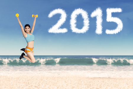 Asian woman holding dumbbells and jumping on the beach with number 2015 photo