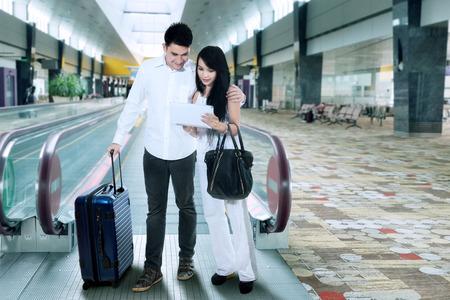 familia viaje: Joven pareja de pie con la maleta en el aeropuerto internacional