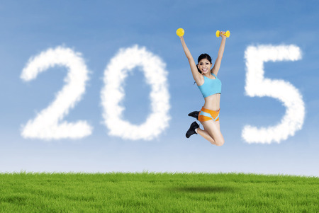 Young woman jumping on meadow while holding two dumbbells and forming number 2015 photo