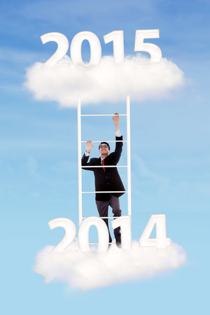 Business person trying to climb upward on ladder over cloud with number 2014-2015 photo