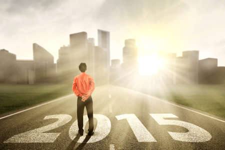 Businessman standing on the road and looking ahead in 2015 photo