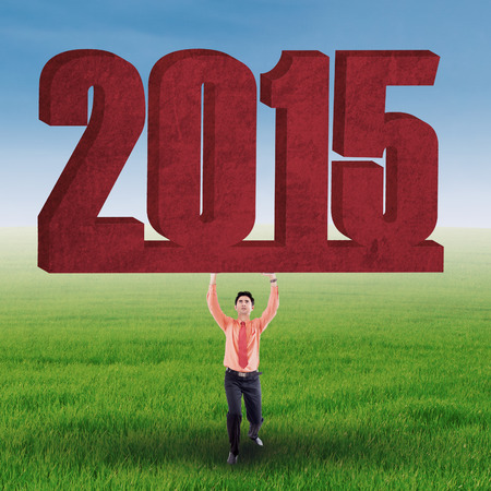 Business person holds number 2015 over his head on meadow, symbolizing the future on his hand photo