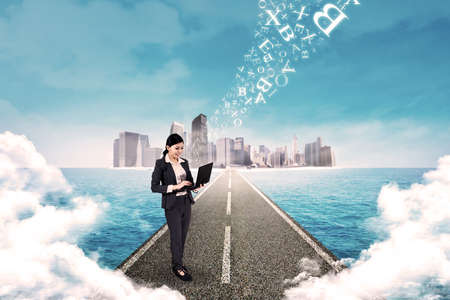 Business woman standing on the road and use laptop to send email photo