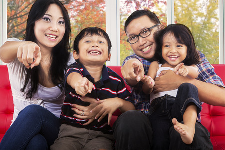 Young asian family smiling and pointing at camera together with autumn background on the window photo