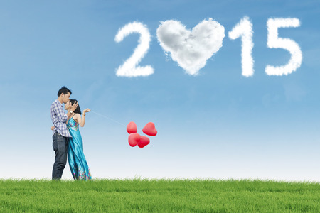 Young man kissing his wife on the field with heart shaped cloud number 2015 photo