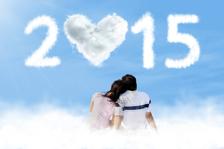 under heart: Rear view couple sitting on cloud under heart cloud shaped number 2015