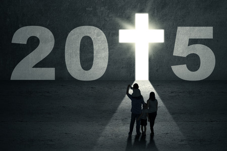 jesus standing: Christian family looking at a door shaped cross with number 2015