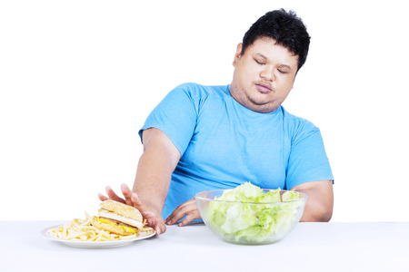 Fat man refuse junk food and choose to eat healthy food