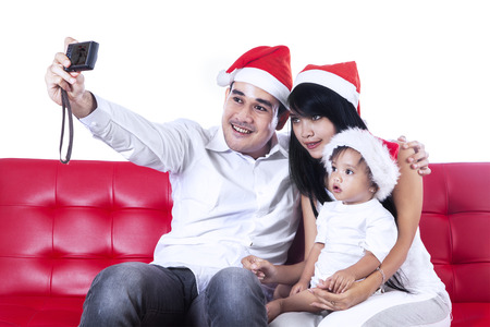 Father taking a christmas family picture on the sofa photo