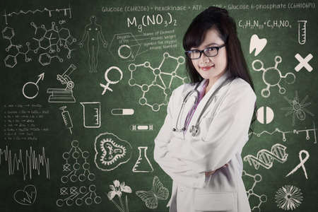 Beautiful female doctor smiling in front of medical background photo