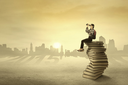 Student sitting on books and looking at her vision on the sky with binoculars photo