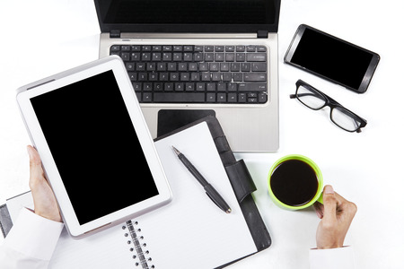 Close up of hands holding digital tablet and coffee in workplace photo
