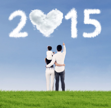 Rear view of happy family standing in field while looking at heart shaped cloud 2015 photo
