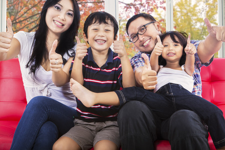 indian happy family: Joyful family sitting on sofa and giving thumbs up at camera with autumn background on the window