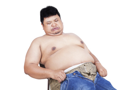 Obese man trying to wear his old jeans. isolated on white background photo