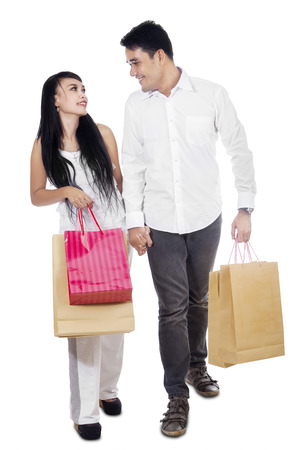 asian shopper: Young couple holding many shopping bags isolated on white