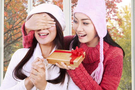 gift giving: Portrait of asian girl wearing jacket giving surprise to her friend at home with autumn background