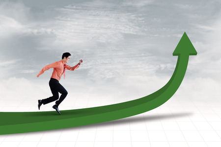 Businessman is running on line chart to achieve profit photo
