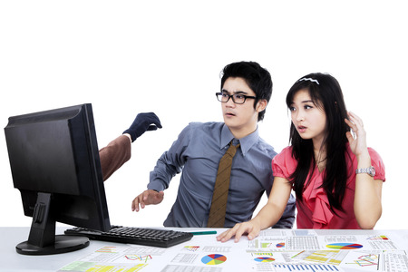 Shocked two asian businesspeople looking hacker at computer