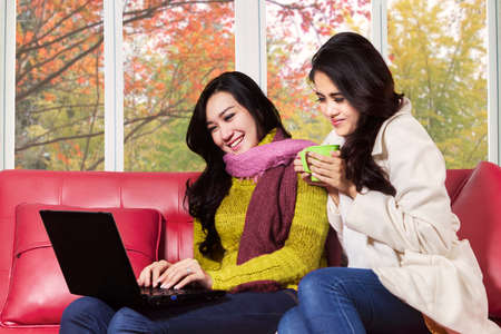 Beautiful asian girlf sitting on sofa while using laptop computer at home in autumn photo