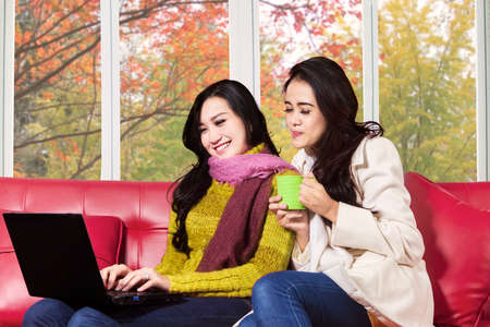 Two young asian girl using laptop together at home with autumn background on the window photo