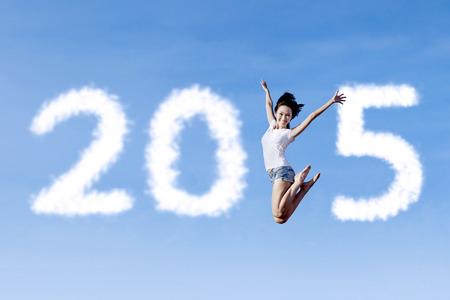 donna volante: Allegro donna asiatica in volo sul cielo e formando il numero 2015