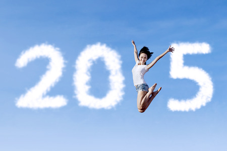 Cheerful asian woman flying on sky and forming number 2015 photo