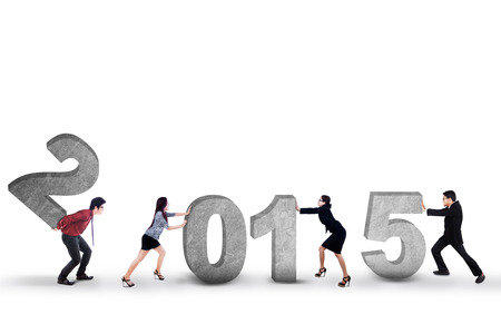 compile: Young business people try to compose number 2015 in studio, isolated over white background