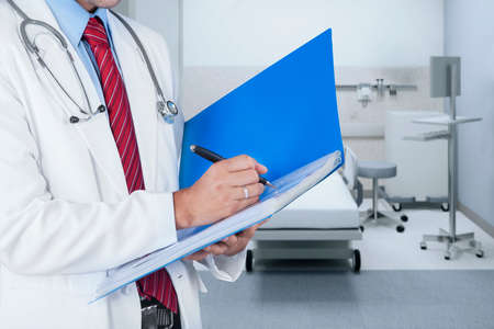 Male doctor writing medical report on a folder in hospital photo