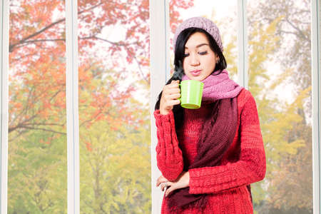 warm drink: Pretty girl wearing jacket and blowing warm drink at home in autumn Stock Photo