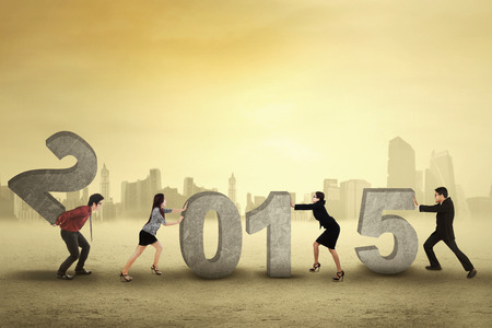 compile: Young business people collaborate to arrange number 2015, symbolizing new business future Stock Photo