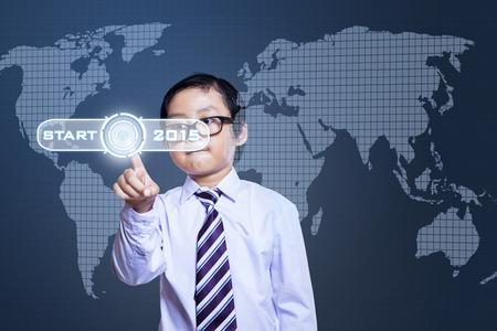 Schoolboy pressing a start button to future 2015 on a futuristic screen photo