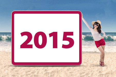 indian summer seasons: Hispanic woman standing on beach next to number 2015 on a board Stock Photo