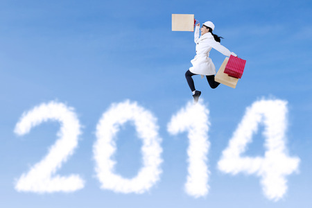 Excited girl with shopping bag jumping announce Happy New year on blue sky photo