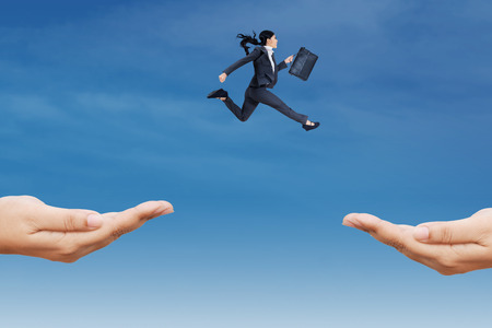 Asian business woman carrying briefcase jump through two hands on the sky to chase her goal photo