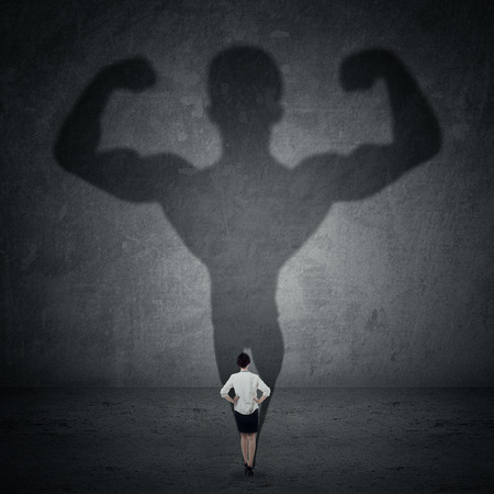 creative strength: Businesswoman casting a shadow of an athlete - business and career strength concept