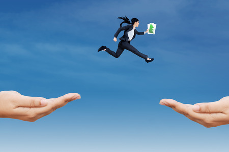 chase: Female entrepreneur carrying business paper jump through two hands on the sky Stock Photo