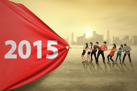 bright future: Young business people try to pull number 2015, symbolizing an effort for progress in 2015