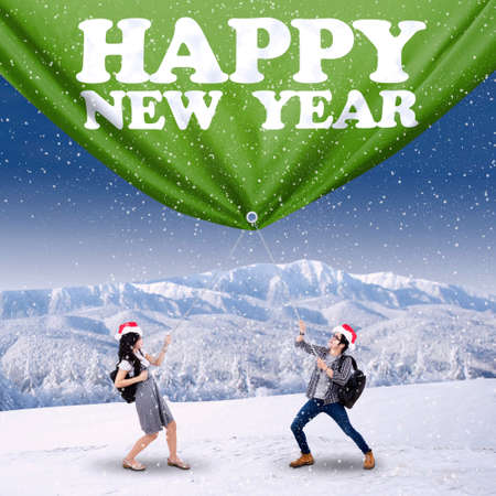 Two college students dragging new year banner on the snowy mountain photo