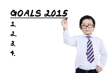 Small business person writes business goals in 2015, isolated over white background photo