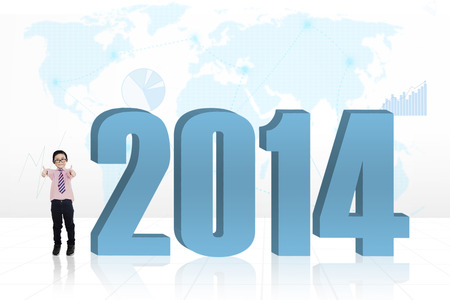 Little child standing next to a new year 2014 with world map background photo